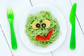 Healthy and creative kids lunch - green spaghetti pasta smiling Royalty Free Stock Photo