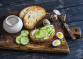 Healthy delicious breakfast or snack - open sandwich with goat's cheese and cucumber and boiled quail eggs. Royalty Free Stock Photo