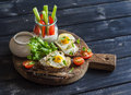 Healthy delicious breakfast or snack -  sandwich with cheese and a fried quail egg, greek yogurt, celery and sweet peppers Royalty Free Stock Photo