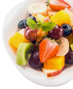 Healthy dessert of fresh tropical fruit salad with colorful berries kiwifruit banana grapes apples and orange garnished with Stock Photography