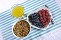 Healthy diet high dietary fiber breakfast with bowl of bran cereal and berries with pineapple juice aerial on white heart plate on Royalty Free Stock Image