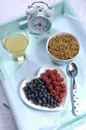 Healthy diet high dietary fiber breakfast on vintage tray vertical with bowl of bran cereal and berries white heart plate aqua Royalty Free Stock Photos