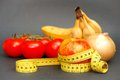 Healthy diet measuring tape wrapped around an apple infront of some tomatoes bananas and an onion for your nutrition food and Stock Photography