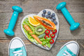 Healthy diet and sport concept with dumbbells trainers and food Royalty Free Stock Photo