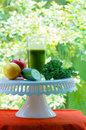 Healthy drink freshly cold pressed green juice in glass with lemon apple cucumber and kale on cake stand green snack concept Stock Images