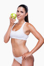 Only healthy eating attractive young woman in white bra and panties holding green apple and smiling while standing isolated on Stock Photo