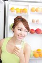 Healthy eating concept diet beautiful young woman drink milk near the refrigerator fruits and vegetables asian model Stock Photo