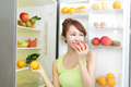 Healthy eating concept diet beautiful young woman near the refrigerator with food fruits and vegetables asian model Royalty Free Stock Images