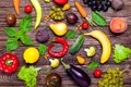 Healthy eating, diet, detox background. Assortment of bright organic fresh fruits and vegetables on the dark wooden table. Vegan,
