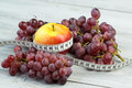 Healthy eating and fitness concept - apple, grapes and measuring tape Royalty Free Stock Photo