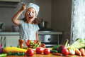 Healthy eating. Happy child girl prepares  vegetable salad in ki Royalty Free Stock Photo