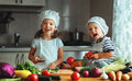 Healthy eating. Happy children prepares  vegetable salad in kitc Royalty Free Stock Photo