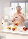 Healthy eating old woman blueberry many fruits on kitchen counter Royalty Free Stock Image