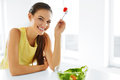 Healthy eating vegetarian woman eating salad food lifestyle close up portrait of young smiling fresh vegetable in modern kitchen Royalty Free Stock Photography