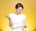 Healthy eating weight loss closeup portrait young attractive happy fit woman in white dress holding green apple measuring her Stock Images