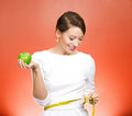Healthy eating weight loss closeup portrait young attractive happy fit woman in white dress holding green apple measuring her Royalty Free Stock Image