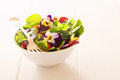 Healthy farm fresh herbal salad herb with leafy greens and nasturtium flowers served in a white bowl with a fork on a wooden white Stock Photography