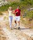 Healthy fit couple actively running outdoors Stock Images