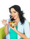 Healthy fit young woman eating a bowl of fresh exotic fruit salad with dark wavy hair holding and mixed colourful for her Royalty Free Stock Images