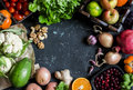 Healthy food background. Assortment of fresh vegetables and fruits on a dark background. Free space for text, top view.