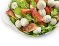 Healthy fresh rucola salad with mozarella and tomato slices served in a white bowl a soft shadow Stock Images