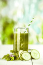 Healthy fresh vegetable juice with cucumbers tall glass of freshly prepared and blended on a white wooden table outdoors in a Royalty Free Stock Photo