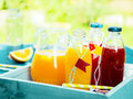 Healthy freshly squeezed fruit juice with bottles of orange citrus blend and fresh berry standing on a turquoise picnic Royalty Free Stock Images