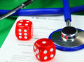 Healthy gamble two dice placed on a doctors medical certificate pad next to his light blue stethoscope asking the question do you Stock Photos