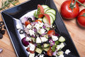 Healthy greek salad on the black plate Royalty Free Stock Photo