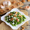 Healthy green beans salad with cottage cheese and walnuts on a white plate and a vintage wooden table. Rustic style