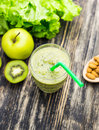 Healthy green smoothie with kiwi, apple on rustic wood background. Royalty Free Stock Photo