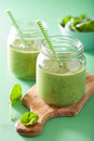 Healthy green spinach smoothie with mango banana in glass jar Royalty Free Stock Photo