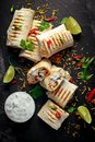 Healthy grilled chicken and parsley wraps, loaded with cheese, served with greek yogurt deep, chillies and lime slices Royalty Free Stock Photo