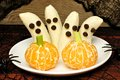 Healthy Halloween banana ghosts and orange pumpkins Royalty Free Stock Photo