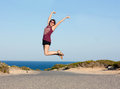 Healthy and happy woman jumping on the road near the sea Royalty Free Stock Images
