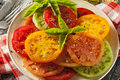 Healthy heirloom tomato salad with basil and dressing Stock Photography