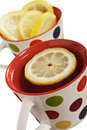 Healthy herbal tea with lemon in polka dot cups on white background Royalty Free Stock Image