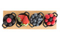 Healthy juicy autumn or fall berries strawberries blueberries blackberries and raspberries displayed in individual ceramic Stock Images
