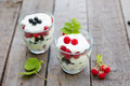 Healthy layered dessert with yogurt black currant and raspberries on wooden background Stock Photos