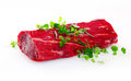 Healthy lean uncooked fillet steak garnished with fresh herbs in preparation for a gourmet meal on a white background Royalty Free Stock Photo