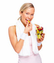 Healthy lifestyle - Fit young woman eating fruit Stock Images