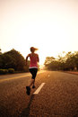 Healthy lifestyle fitness sports woman running at sunrise road Royalty Free Stock Photography