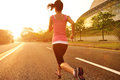 Healthy lifestyle fitness sports woman running at sunrise road Royalty Free Stock Images