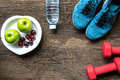 Healthy lifestyle sport equipment fitness, sneakers, green apple, fresh water and healthy food on old wood background.