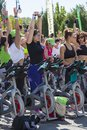 Healthy lifestyle using stationary bikes group of women stretching bicycles for cardio training during a public cycling exercise Stock Images