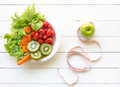 Healthy lifestyle for women diet with measuring tape, vegetable fresh, green apples on white wooden. Royalty Free Stock Photo