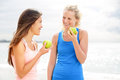 Healthy lifestyle women eating apple after running two beautiful girlfriends talking enjoying fruit jogging training on Royalty Free Stock Images