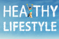 Healthy lifestyle word with a woman fitness young jumping clouds shaped of Royalty Free Stock Photography