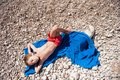 Healthy little kid in red shorts lying on blue towel on beach in hot summer day Royalty Free Stock Photo