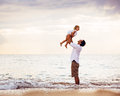 Healthy loving father and daughter playing together at the beach sunset happy fun smiling lifestyle Stock Images